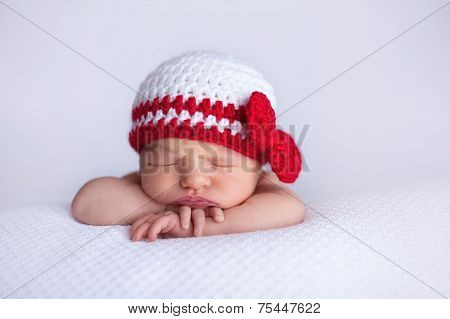 Newborn Baby Girl Wearing A White And Red Crocheted Cap