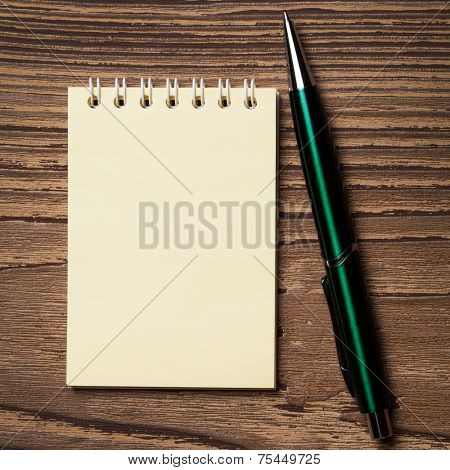 Pen and notebook on wooden table.
