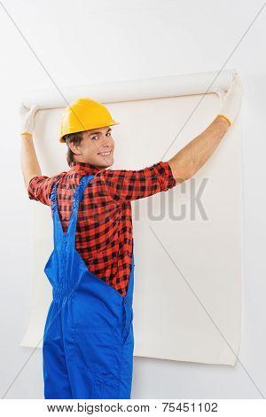 Smiling repairman gluing wallpaper