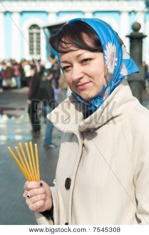Young Beautiful Woman With Tapers In Hand And Shawl On Head