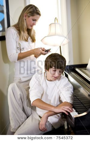 Teenage Boy By Piano With Sister Texting Behind