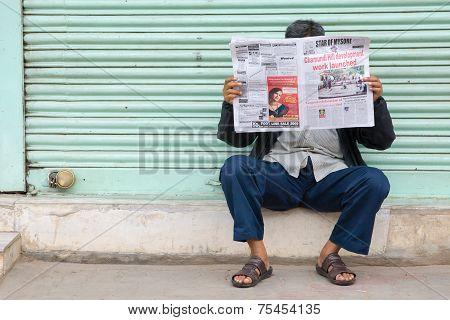Indian man reading newspaper.