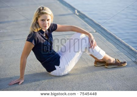 Teenage Girl Sitting On Dock By Water