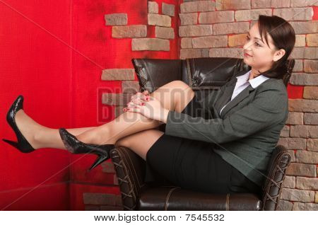 Young Beautiful Business Woman Sitting In Armchair In Studio Interior