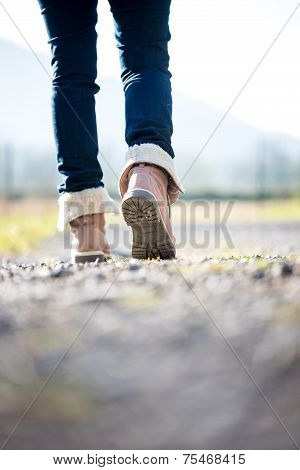 Woman In Jeans And Boots Walking Along A Rural Path