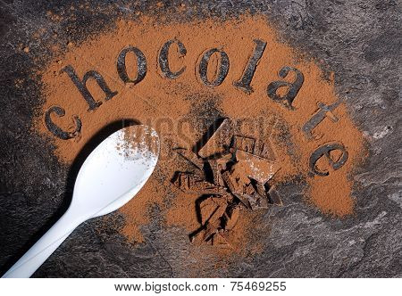 Modern Aerial View Of Chocolate On Black Slate Bench Top Table With Pale Blue Spoon, Spelling Letter
