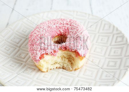 Bitten delicious donut on plate on wooden table close-up