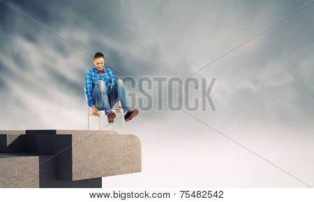 Young woman in shirt sitting in chair on building roof