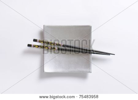 pair of black chopsticks on silver plate