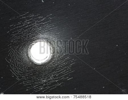 Bullet hole in thick sheet metal from the back view