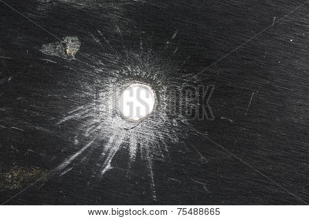 Bullet hole in thick sheet metal from the front view