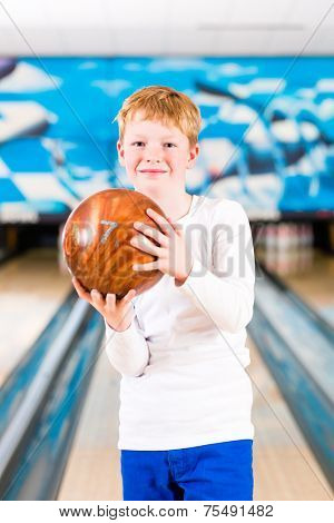 Child bowling with ball in alley