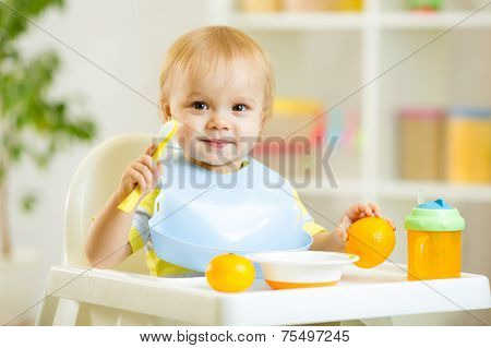 smiling baby child boy eating itself with spoon
