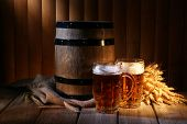 stock photo of fermentation  - Beer barrel with beer glasses on table on wooden background - JPG