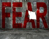 image of overcoming obstacles  - red fear word on old mottled concrete wall with large blank hole overcoming fear concept - JPG