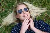 stock photo of splayed  - Lovely young lady relaxing on the grass and wearing heart shaped sunglasses - JPG