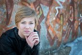 Picture of depressed teen girl in leather jacket, with graffiti wall as background.
