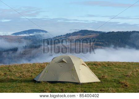 Mountain landscape with tourist tent on a meadow