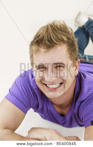 Youth Lifestyle Concept: Closeup Portrait Of Smiling Tanned Caucasian Handsome Man Laying On Floor W
