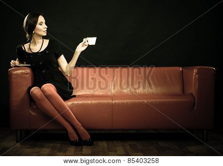 Retro Woman Holds Tea Cup Sitting On Sofa