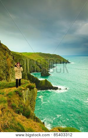 Irish Atlantic Coast. Woman Tourist Standing On Rock Cliff