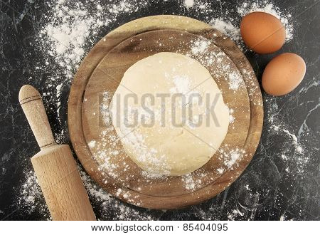 Freshly Prepared Dough On A Wooden Board. Rolling Pin And Egg On Table. Top View.