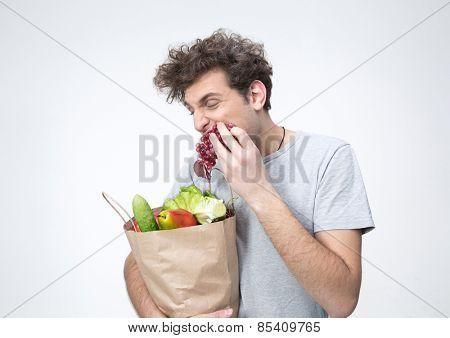Handsome man holding a bag full of groceries and eating grapes