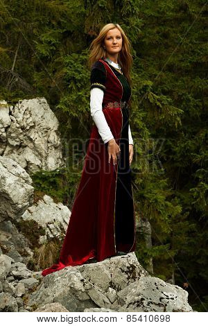 woman blonde hair in a historical gown is standing on rocks amids a breathtaking forestral landscape