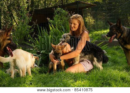 woman with blonde hair is playing lovingly with a bunch of dogs in a backyard garden with grass