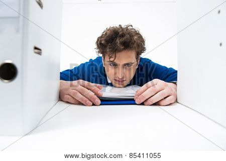 Tired businessman sitting at the table with documents in office