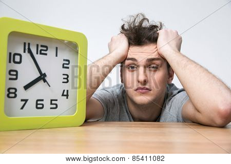 Tired young man sitting at the table with big clock