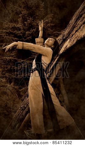 girl in a historical costume posing in a dramatic gesture amids the forest surroundings next to an o