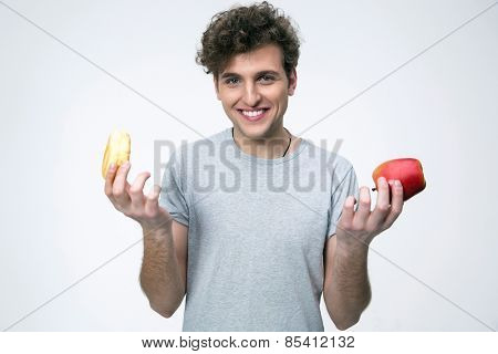 Smiling man holding apple and donut over gray background