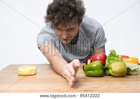 Young man choosing healthy vegetables food or unhealthy donut