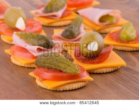 Crackers for snacks, with cheese, tomato, pickle, pepperoni, olives - on dark wood tabletop