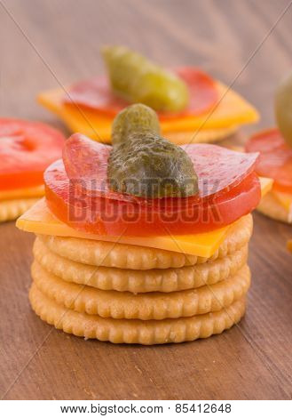 Stack of crackers, top one loaded with cheese, tomato, pepperoni and pickle; on dark wood table top