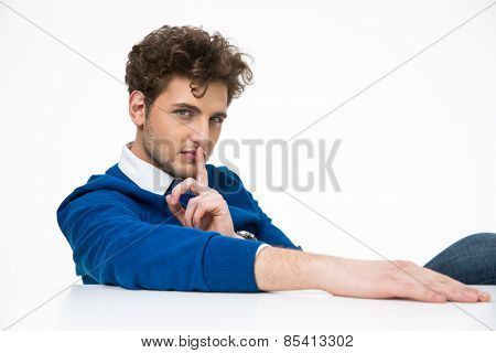 Businessman sitting at the table with finger over lips