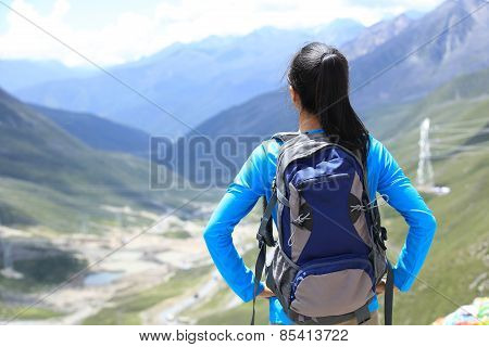 cheering hiking woman enjoy the beautiful view at mountain peak in tibet,china