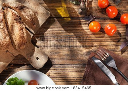 Top view of italian food on wooden table - bread, olive oil and tomatos with basil