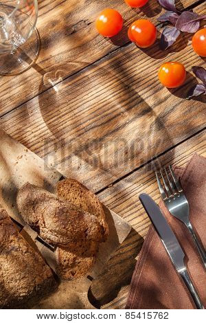 Top view of empty wineglass with bread on served wooden table