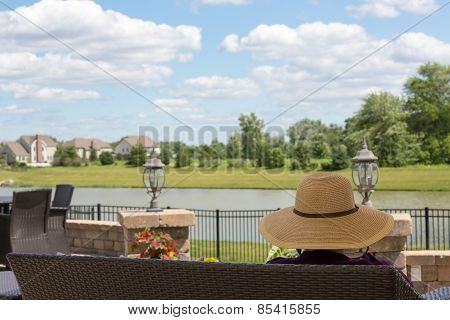Woman In A Sunhat Sitting On A Patio Bench
