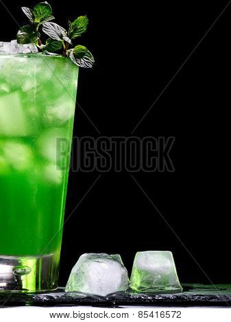 Green drink  with crushed ice and mint leaf on dark background.