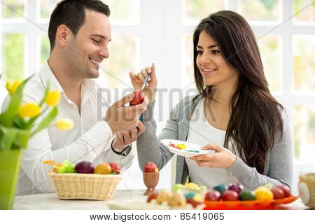 Young man and woman painting Easter eggs, couple in love on Easter