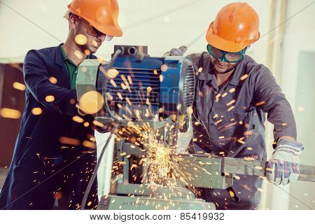Worker welding in industrial background at factory