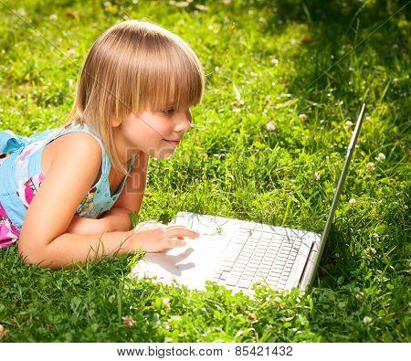Little girl usng laptop in a summer garden
