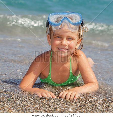 Happy little girl wearing snorkeling mask lying in the sea