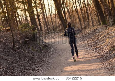 Female runner in the forest.