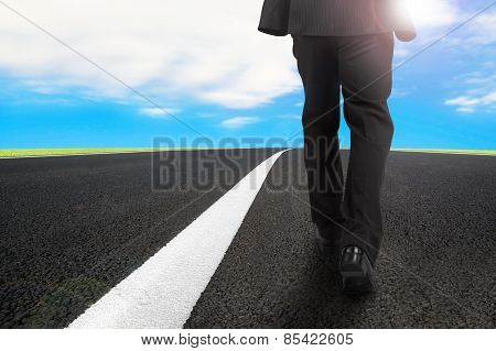 Businessman Walking On Asphalt Road With Sunlight Blue Sky