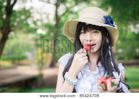 A Cute Asian Thai Girl With Vintage Clothings Is Eating Strawberry She Picked Up In The Forest