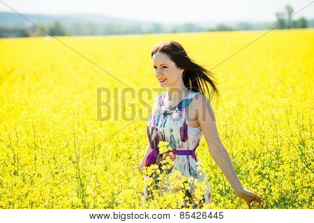 Young woman in rapeseed field